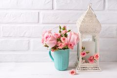 Pink roses flowers in blue cup and decorative white  lantern aga Royalty Free Stock Image