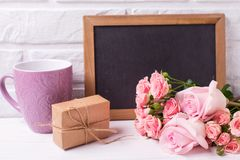 Pink roses flowers, empty blackboard,  box with present and viol. Et cup on white wooden background. Floral still life.  Selective focus. Place for text Royalty Free Stock Photos