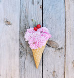 Pink roses flowers topped with a red cherries in ice cream cone on rustic wooden background Stock Photography