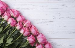 Pink roses on white wooden background with copy space. Top view. Royalty Free Stock Photos