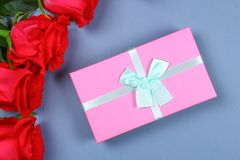 Pink roses with a gift box tied with a bow. Template for March 8, Mother's Day, Valentine's Day. Pink roses with a gift box tied with a bow. Template for March Stock Photo