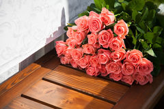 Pink roses are a gift. Flowers lie on a wooden bench. Pink roses are a gift. Flowers lie on a wooden bench outdoor on sunny day Stock Photos