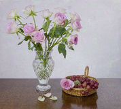 Pink Roses and grapes. View of a  pink roses in a vase with grapes in a basket Royalty Free Stock Image