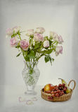 Pink Roses and grapes. View of a  pink roses in a vase with grapes in a basket Royalty Free Stock Photo