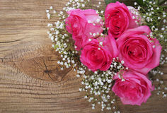 Pink Roses and Gypsophila on Wooden Background Stock Images