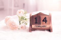 Pink roses lay on the table near calendar with the date of Febru stock image