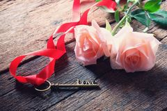 Pink roses and Love key shape on vintage wooden floor under soft warm light. Backdrop for Valentine& x27;s day. Love concept. Copy space stock images