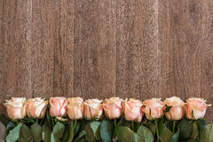 Pink roses lying on wooden background. Background for spring themes. Stock Photography