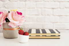 Pink Roses Mock Up. Styled Photography. Brick Wall Product Display. Strawberries On Striped Design Notebooks. Vase With Pink Roses stock image