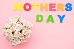 Pink roses with for Mothers day on background of text, flat ray. Copy space. Top view. royalty free stock photography