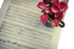 Pink roses on musical notes Stock Photography