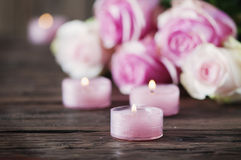 Pink roses and pinl candles on the wooden table Stock Photo