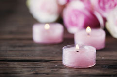 Pink roses and pinl candles on the wooden table Stock Images