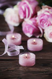 Pink roses and pinl candles on the wooden table Royalty Free Stock Photography
