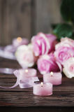 Pink roses and pinl candles on the wooden table Stock Photography