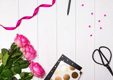 Pink roses, ribbon, notepads with gold dots, paper hearts and ot. He objects on the white wooden table. Top view royalty free stock image