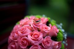 Pink roses and rings. Big Bouquet and Two Wedding Rings. Goods for wedding. This photo is perfect for magazines, shops dealing with wedding dresses ceremonies Stock Photography