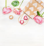 Pink roses with shopping bag and chocolates heart on white wooden background, top view. Love symbol. stock photography