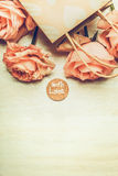 Pink Roses in shopping bag with love Message Sign on light background, top view.Pastel toned. Stock Photos
