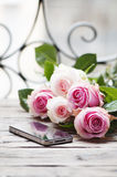 Pink roses and smartphone on the wooden table Stock Photos