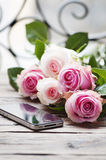 Pink roses and smartphone on the wooden table Stock Image