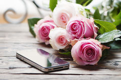 Pink roses and smartphone on the wooden table Stock Photo
