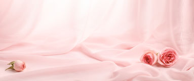 Pink roses on soft silk. Pink silk background royalty free stock photos