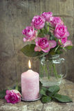 Pink roses. Still life with pink roses and candle. Coated colored texture stock photography
