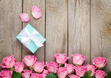 Pink roses and valentines day gift box over wooden table Stock Photo
