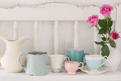 Pink roses in vase and dinnerware Royalty Free Stock Images