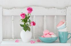 Pink roses in vase and dinnerware on  wooden shelf Stock Photo
