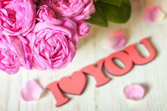 Pink roses in a vase. Pink roses and petals on white wooden desk and red wooden word Royalty Free Stock Photos