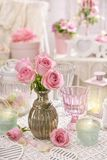 Pink roses in vase on the table in shabby chic style interior Stock Image