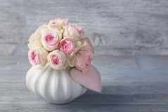 Pink roses in a vase. On a wooden background royalty free stock photos
