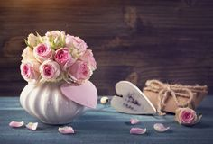 Pink roses in a vase. On a wooden background royalty free stock photo