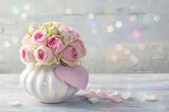 Pink roses. In a vase on a wooden background stock photography