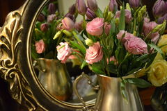 Pink roses in a vase. Pink and yellow roses reflected in a mirror Royalty Free Stock Image