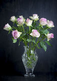Pink Roses. View of a vase of pink roses on a dark background Royalty Free Stock Photography