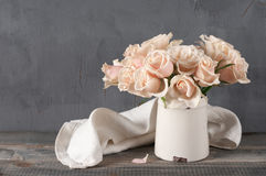 Pink roses in vintage vase. Bouquet of delicate pink roses in vintage tin vase on grey rustic wooden background. Shabby chic home decor stock images