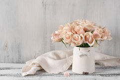 Pink roses in vintage vase. Bouquet of delicate pink roses in vintage tin vase on white rustic wooden background. Shabby chic home decor Royalty Free Stock Photo
