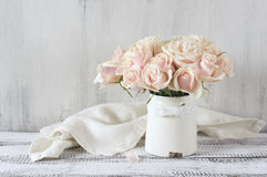 Pink roses in vintage vase. Bouquet of delicate pink roses in vintage tin vase on white rustic wooden background. Shabby chic home decor Stock Images