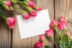 Pink roses and white card with a place for a text on a wooden ta royalty free stock photo