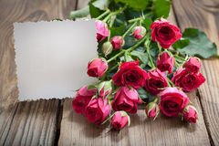 Pink roses and white card with a place for a text on a wooden ta Stock Photo