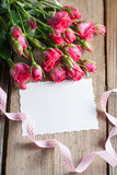 Pink roses and white card with a place for a text on a wooden ta Stock Photography
