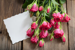 Pink roses and white card with a place for a text on a wooden ta Stock Image