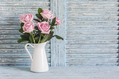 Pink roses in white enamel jug on a blue rustic background. Free space for text. Vintage style stock image
