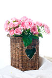 Pink roses in a wicker basket and linen fabric Stock Photos