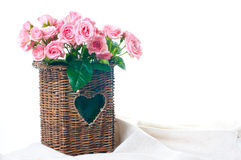 Pink roses in a wicker basket and linen fabric Stock Photo