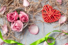 Pink roses and a wicker heart with decorations on the table-a concept of love and congratulations for a loved one.  royalty free stock photography