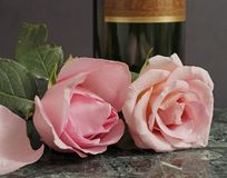 Pink roses and wine. Close up of roses on a green marble slab, with a wine bottle in the background Stock Photo